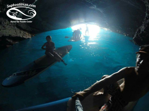 On our knees in the blue cave paddle boarding Ibiza